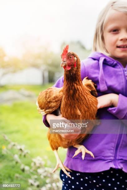 Niña con orgullo con una gallina en un campo.
