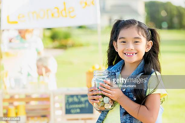 Little girl proudly sells lemonade in her front yard