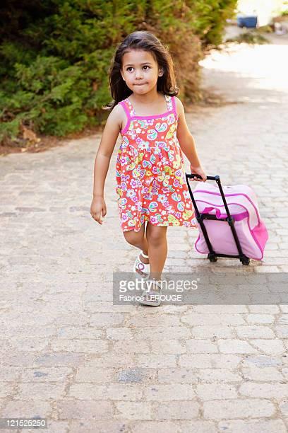Little girl pulling a bag