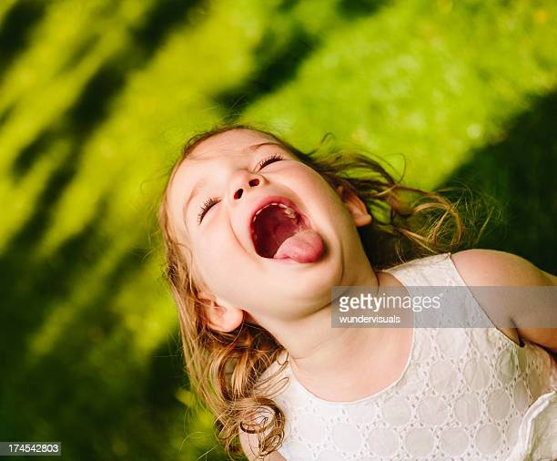 little girl pulling face and sticking tongue out - little girl sticking out tongue stock photos and pictures