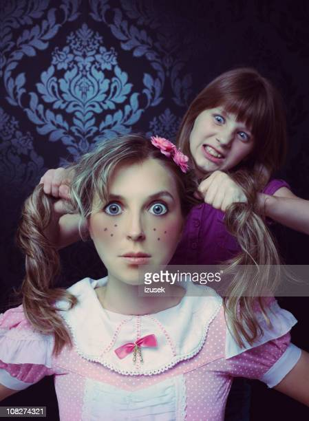 little girl pulling on doll's hair - izusek stock pictures, royalty-free photos & images
