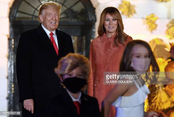 Little girl pulls away a boy dressed as the president who paused to take a photo in front of US President Donald Trump and First Lady Melania Trump...