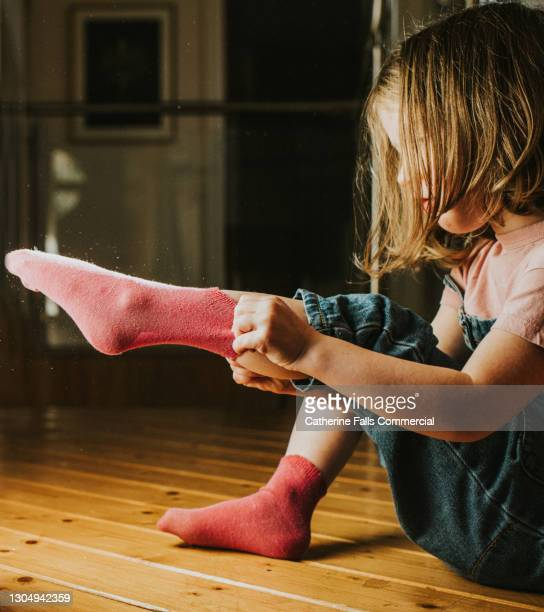 little girl pulls on a pink sock - human joint stock pictures, royalty-free photos & images
