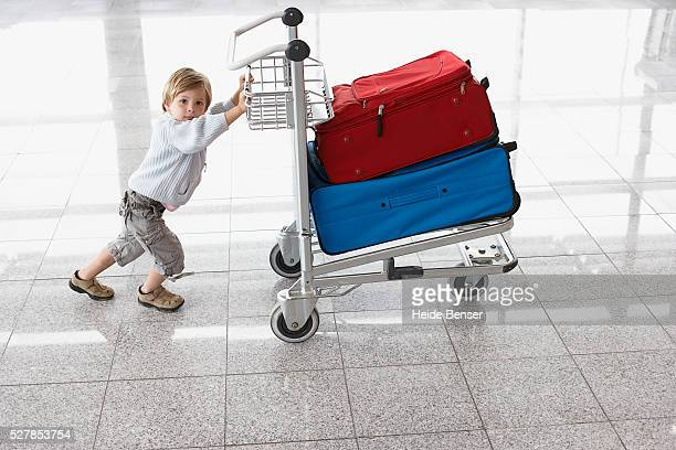 Little girl pushing baggage cart