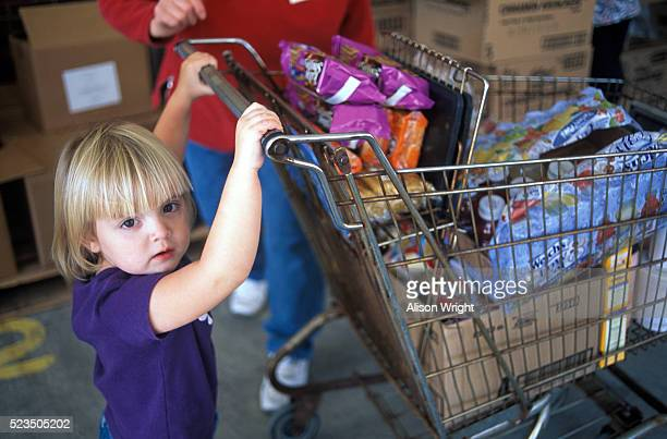 little girl pushing cart at foodbank - poverty in america stock pictures, royalty-free photos & images
