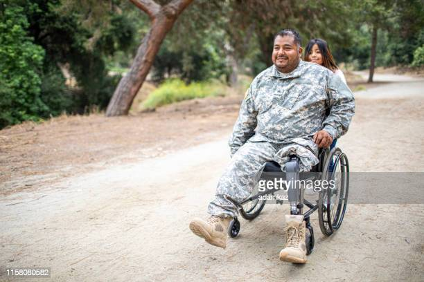 little girl pushing her dad in a wheelchair - injured soldier stock photos and pictures