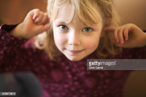 little girl putting fingers in ears - fingers in ears stock pictures, royalty-free photos & images