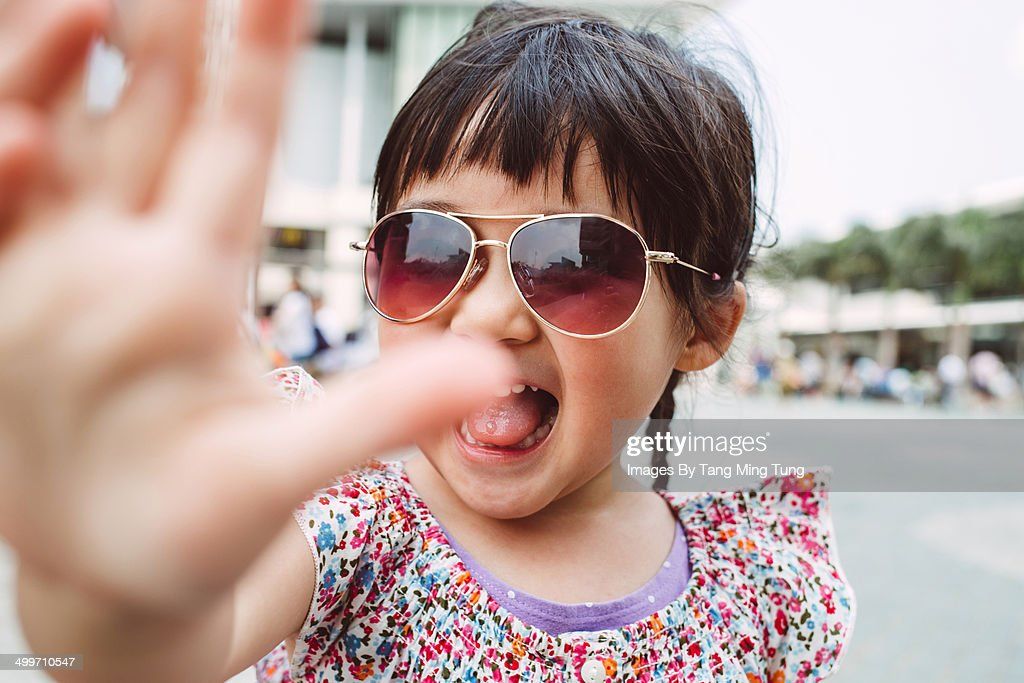 Little girl putting her hand in front of camera : Stock Photo