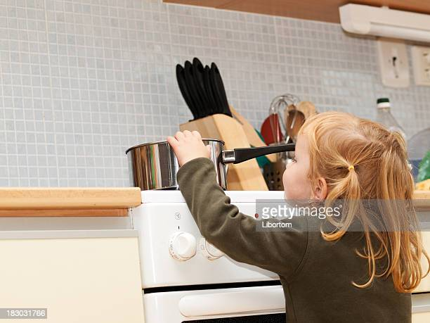 Little girl putting her hands in a pot on a stove