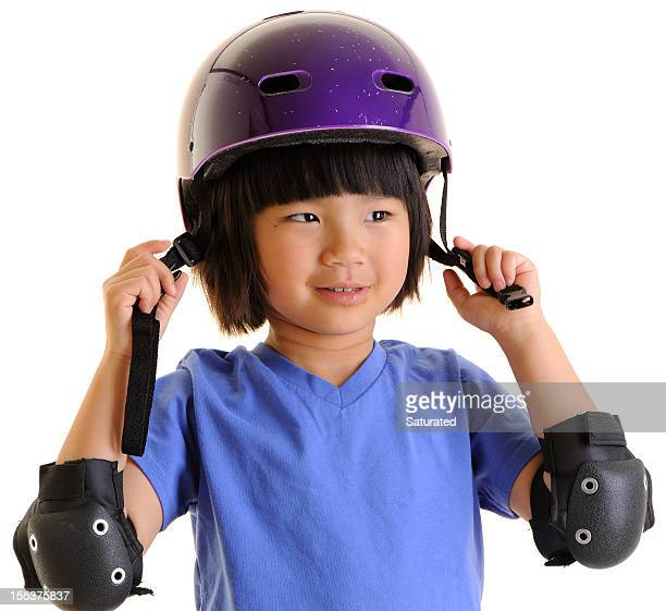 Little Girl Putting on Helmet and Elbow Pads