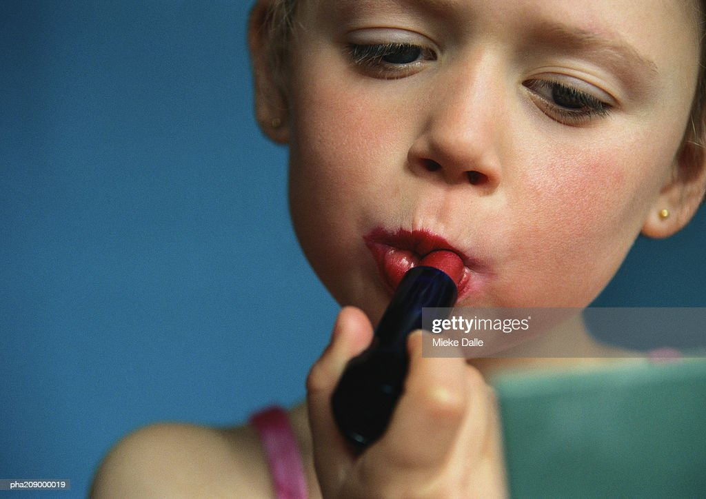 Little girl putting on lipstick, close-up. : Stockfoto