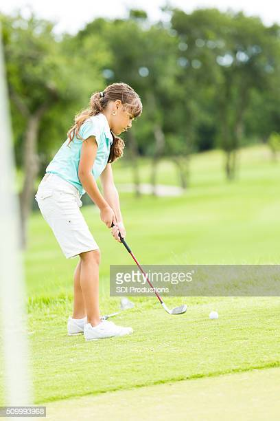 Little girl putts ball at golf course