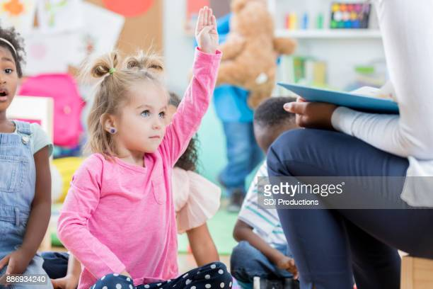 Little girl raises hand during story time at day care