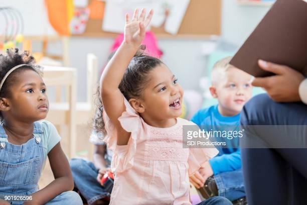 Little girl raises hand during story time