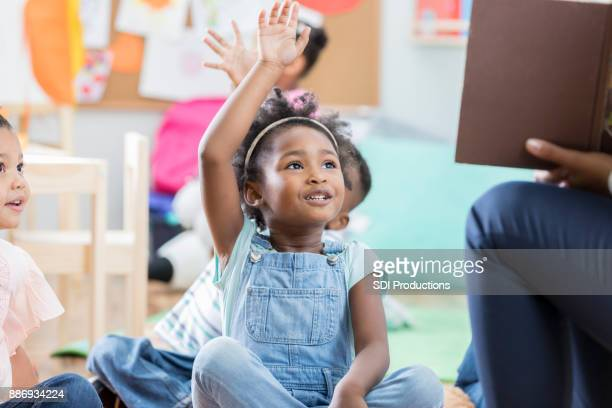 little girl raises her hand during story time - storyteller stock pictures, royalty-free photos & images