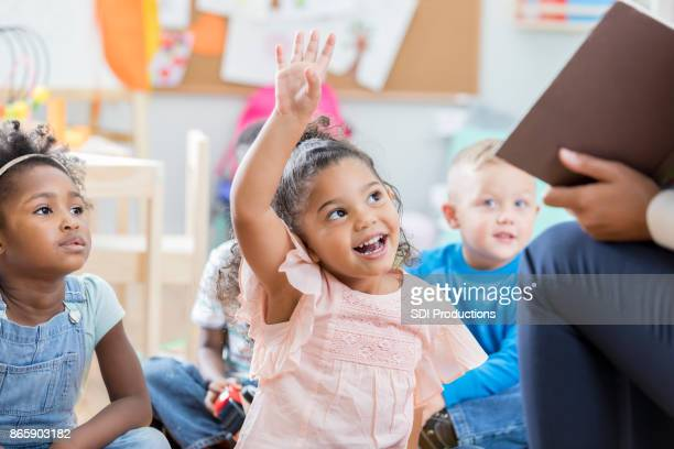 little girl raises her hand in class - classroom stock photos and pictures