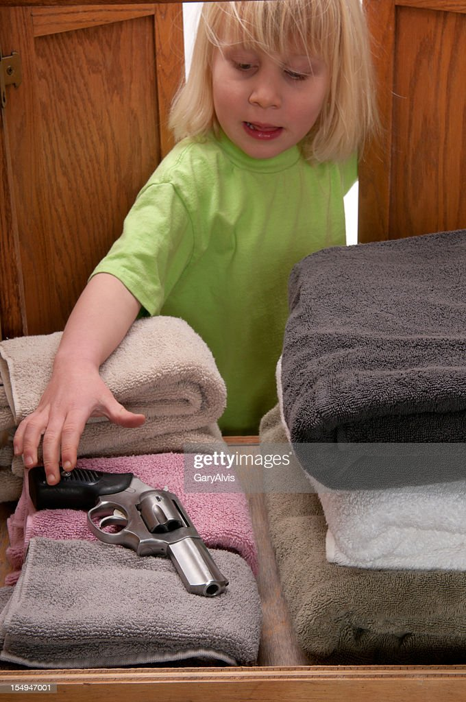 CHILD SAFETY SERIES-#4 little girl reaching for gun : Stock Photo