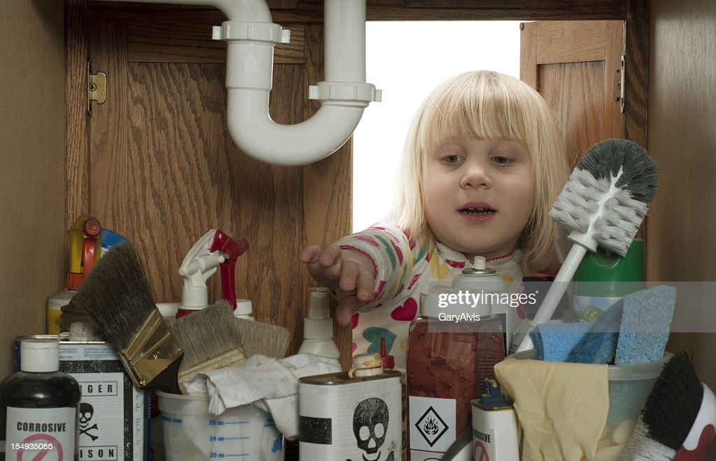 CHILD SAFETY SERIES-#2 little girl reaching under sink : Stock Photo