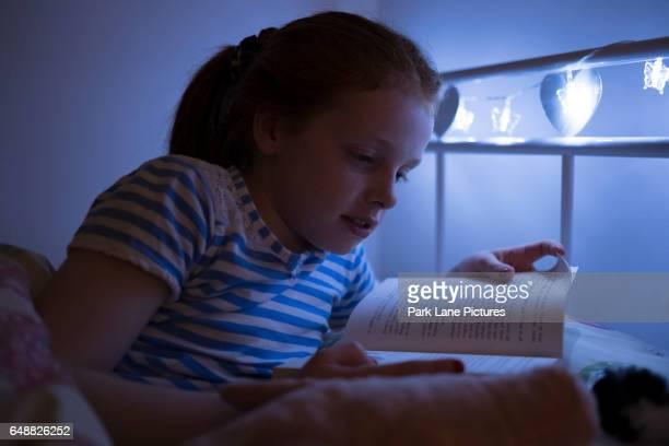 a little girl reading a book at bed time. - ginger lee fotografías e imágenes de stock