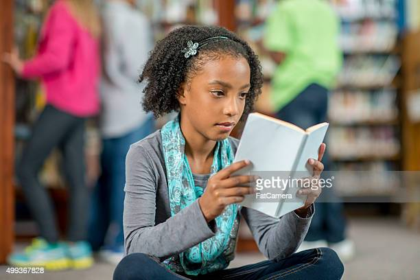 Little Girl Reading a Book in the Library