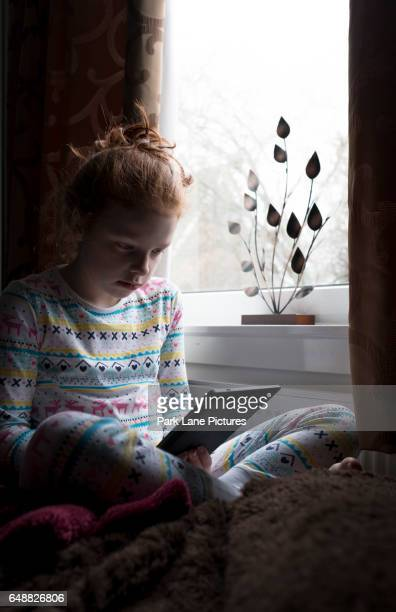 A little girl reading a book on a tablet.