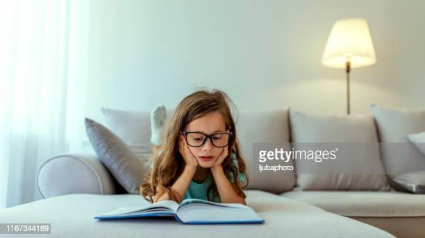 little girl reading a child book at home - ler imagens e fotografias de stock