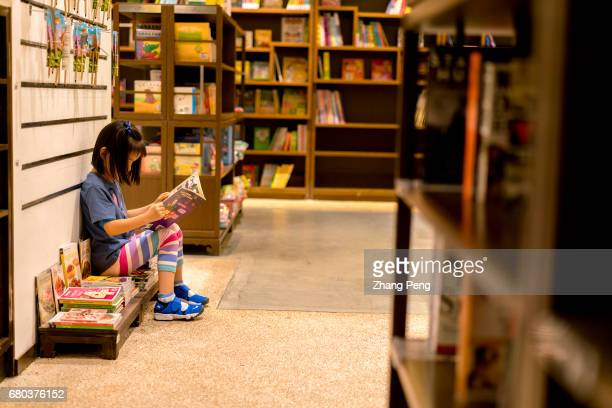 Little girl reading a children's book in a book store According to a recent survey by China News Publishing Research Institute in 2016 85% of Chinese...