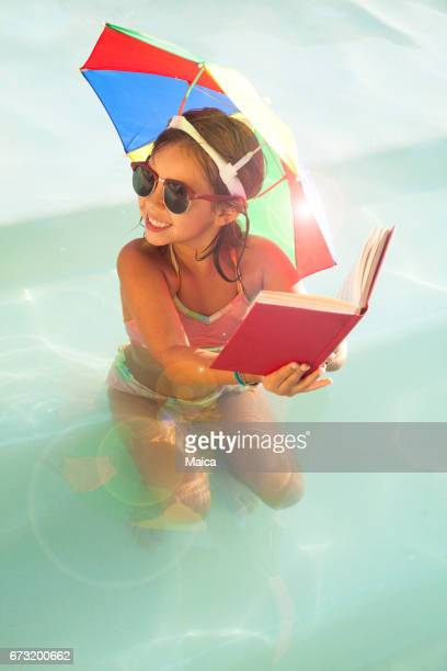 Little girl reading at the swimming pool