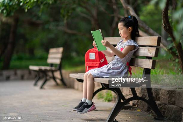 little girl reading book - good posture stock pictures, royalty-free photos & images