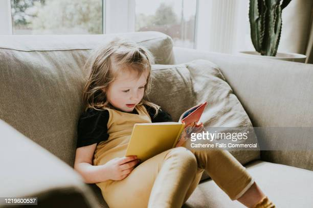little girl reading - preschool child stock pictures, royalty-free photos & images