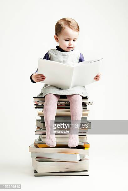 Little girl reading seated on a pile of books