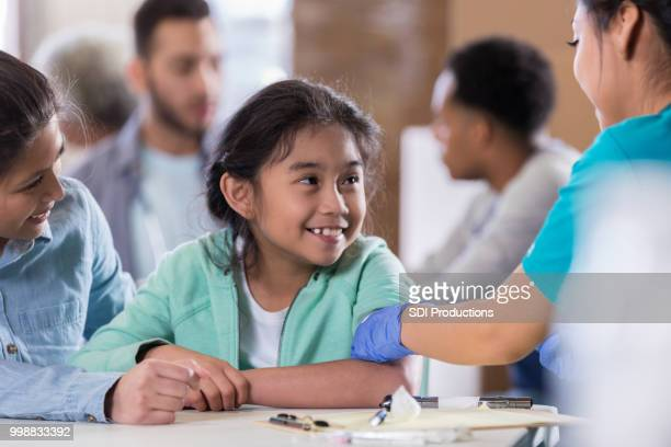 little girl receives flu vaccine - flu shot stock photos and pictures