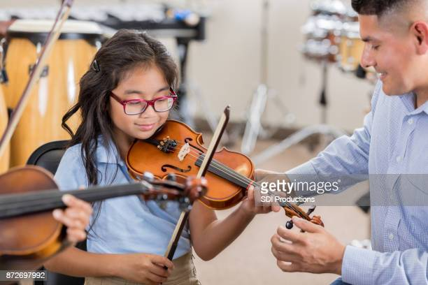 Little girl receives instruction during violin class