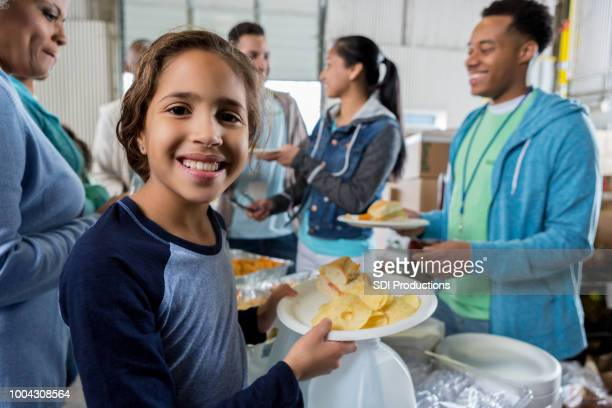 little girl receives meal during food bank charity drive - homeless shelter stock pictures, royalty-free photos & images
