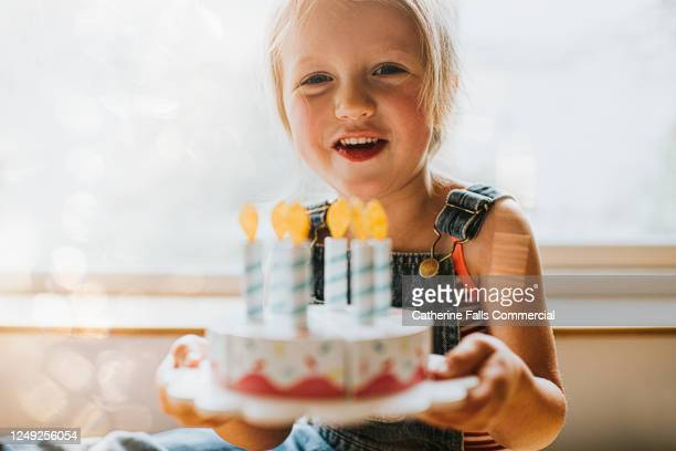 little girl receiving a birthday cake - celebratory event stock pictures, royalty-free photos & images