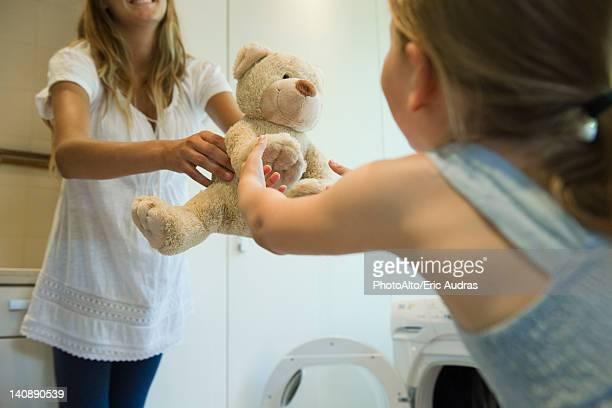 Little girl receiving freshly cleaned teddy bear from mother