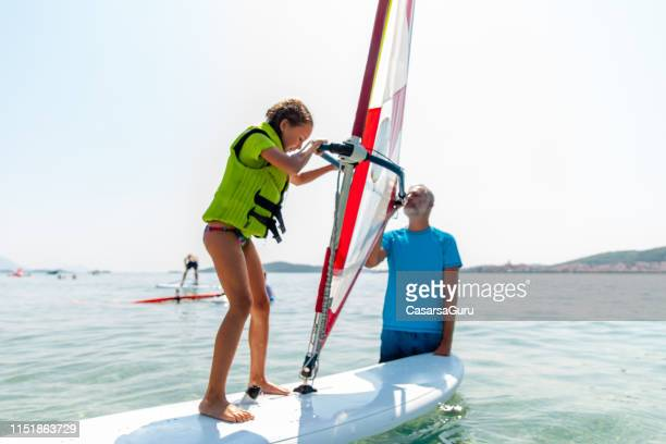 little girl receiving her first windsurf lessons - windsurfing stock pictures, royalty-free photos & images