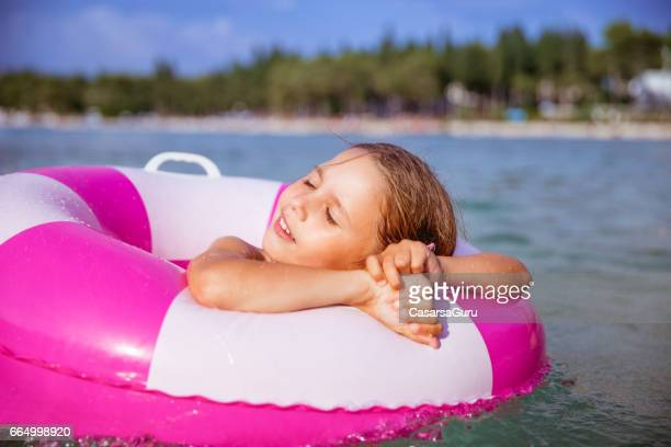 Little Girl Relaxing In The Swimming Tube Floating On The Sea Water - Close Up