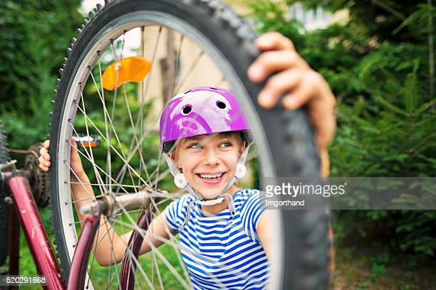Little girl repairing a bicycle