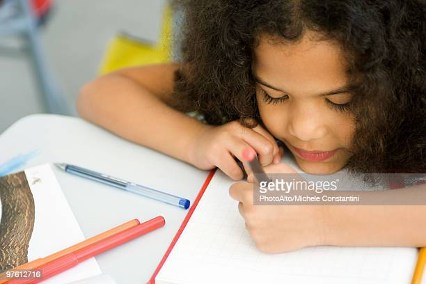 Little girl resting head on desk, drawing on graph paper