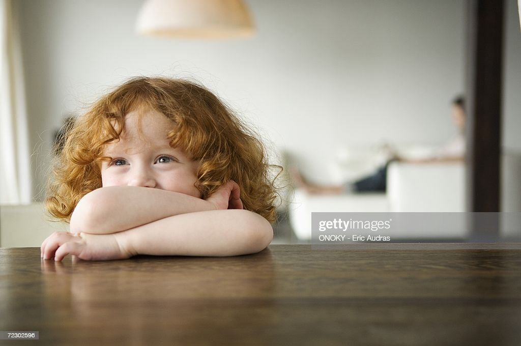 Little girl resting her arms on a coffee table : Stock Photo