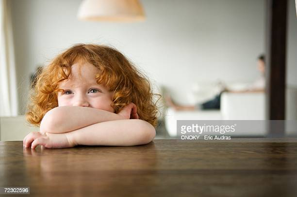 Little girl resting her arms on a coffee table