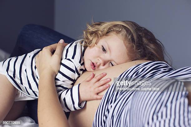 little girl resting her head and hand on mothers pregnant stomach - family with one child stock pictures, royalty-free photos & images