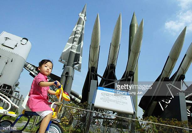 A little girl rides her tricycle past a stack of scrapped missiles the South Korean Nike the US Hawk and the North Korean Scud displayed at a war...