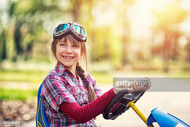 little girl riding a go-kart bike in park. - flying goggles stock pictures, royalty-free photos & images