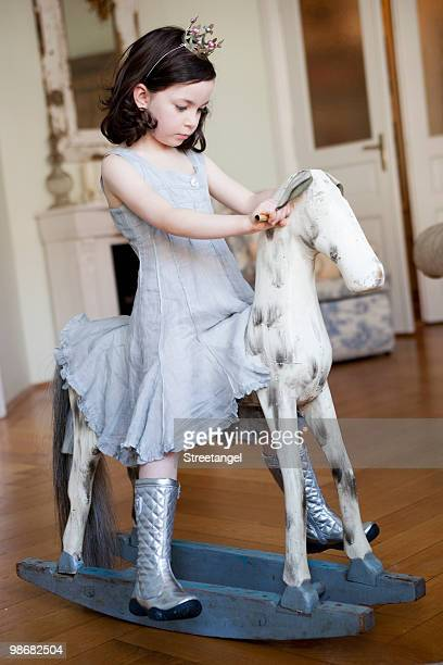 little girl riding a rocking horse