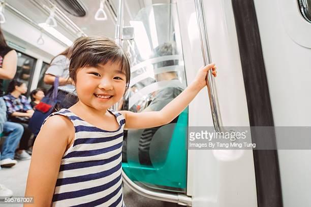 Little girl riding a train joyfully