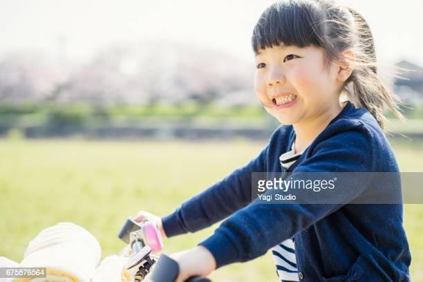 屋外で小さな女の子乗馬の自転車。