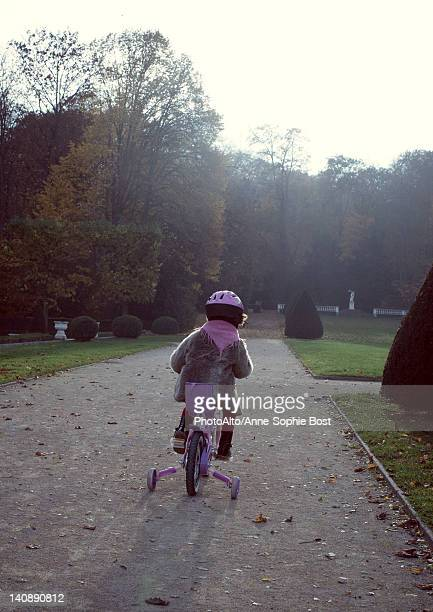 Little girl riding bicycle, rear view