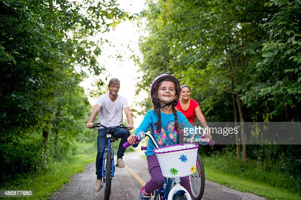 Little Girl Riding Bike with her Parents